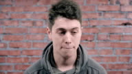 Young man in grey hoody speak on camera. Brick wall background. Audition video