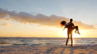 A young man in love at the hands circling his bride. On the beach at sunset. Slow motion video video
