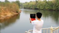 young man in nature take photo with tablet video