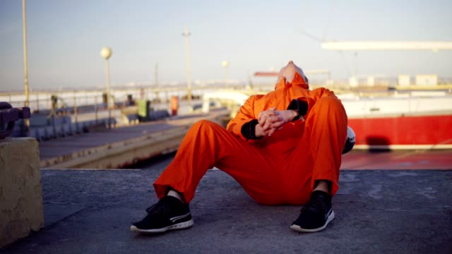 Young man in orange uniform sitting during his break by the sea in the harbor video
