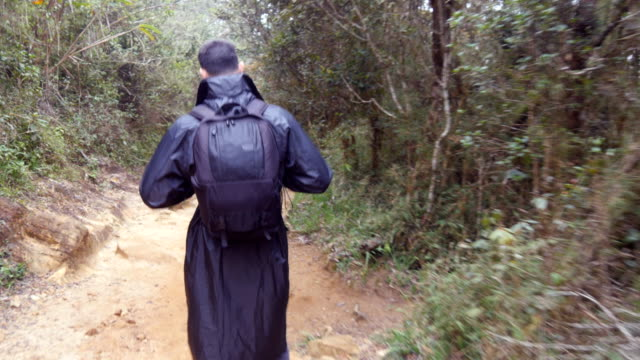 Young man in raincoat going on wood trail during travel. Hiking guy with backpack walking in tropical wet forest. Follow to male tourist stepping on the jungle path. Rear back view video