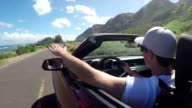 CLOSEUP: Young man in red convertible driving along coastal road in sunny Hawaii video