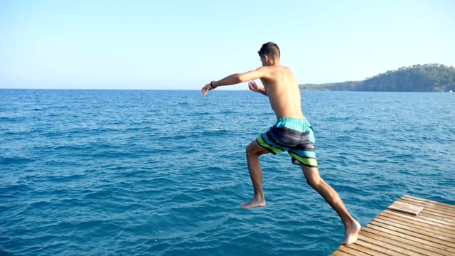 Young man in shorts jumps feet first in the Mediterranean sea waters in slo-mo video