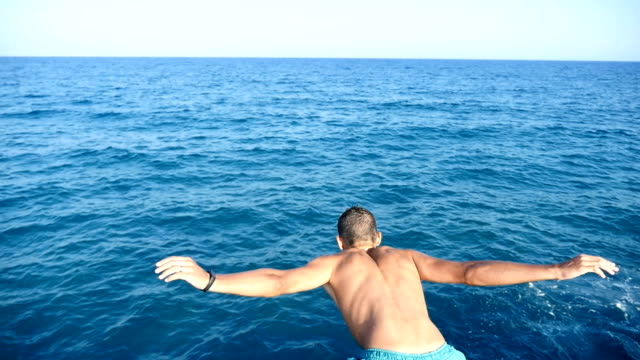 Young man in shorts jumps head first in the Mediterranean sea waters in slo-mo video