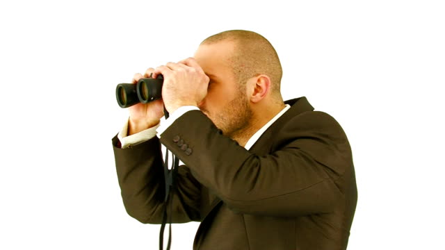 Young man in suit looking through binoculars. Close-up video