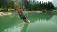 SLOW MOTION: Young man in swimwear jumping over the sun into the beautiful green mountain lake in sunny summer video