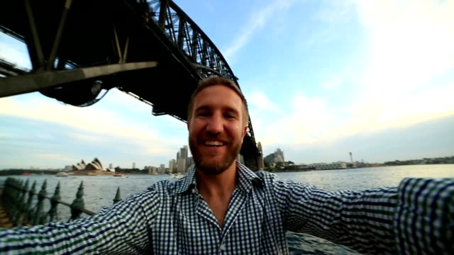 Young man in Sydney harbour, takes a selfie portrait video
