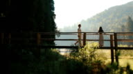 A young man in traditional ukrainian clothes embraces and kisses beautiful young woman on the wooden bridge in mountains. Fairy-tale love story in Carpathians video