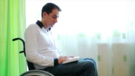 Young man in wheelchair reading a book video