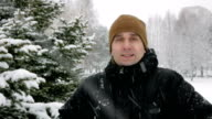 A young man in winter is cold in the forest near the spruce. Big snowfall. He's breathing on his hands, rubs and wears gloves with a hood. Snowy landscape. He looks into the camera video
