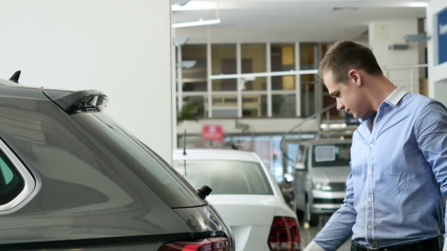 Young man inspecting the trunk of a car video