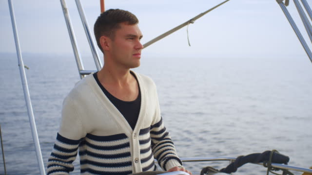 Young man is driving a sailing boat in the sea. video