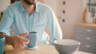 Young man is holding a cup of tea having a conversation in the kitchen in the morning. Slow motion, Steadicam shot video