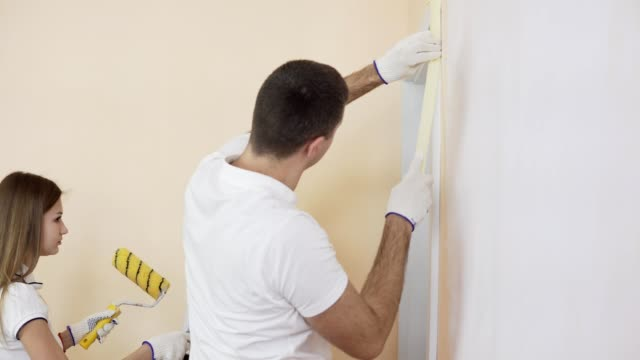 A young man is preparing to paint a white wall by masking off the door with white painter's tape. A woman standing near with a roller preparing to paint the wall video