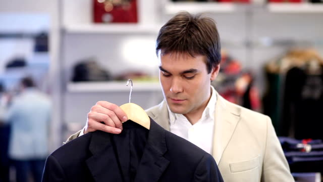 Young man is shopping for clothes video