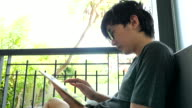 Young man is using a tablet computer while sitting on a sofa at home video