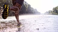 SLO MO Young man jogging in a shallow river video