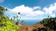 SLOW MOTION: Young man jogging in jungle mountains overlooking valley and ocean video
