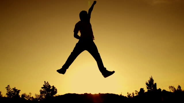 SLOW MOTION: young man jumping at sunset video