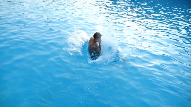 Young man jumps feet first in the blue waters of the sea in slow motion video