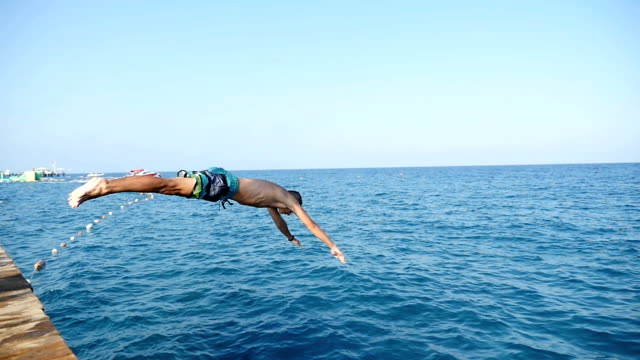 A young man jumps from a pier into the sparkling sea of Turkey resort in slo-mo video