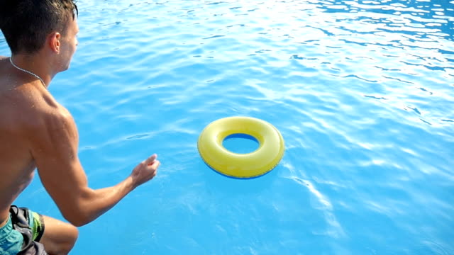 Young man jumps into an inflatable ring into the sea feet first in slow motion video