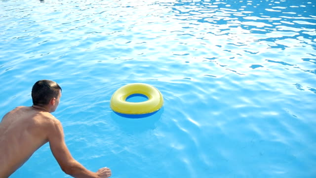 Young man jumps straight into inflatable ring in the blue sea waters in slo-mo video