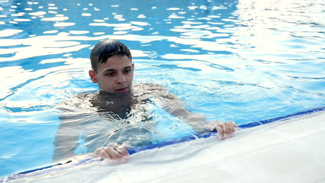 Young man keeps the edge of a pool being in water, enjoying his life in slo-mo video