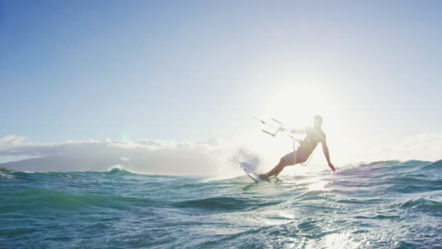 Young man kitesurfing on surfboard in blue ocean at sunset video