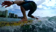 SLOW MOTION: Young man learning to surf at famous surf spot in Waikiki beach video