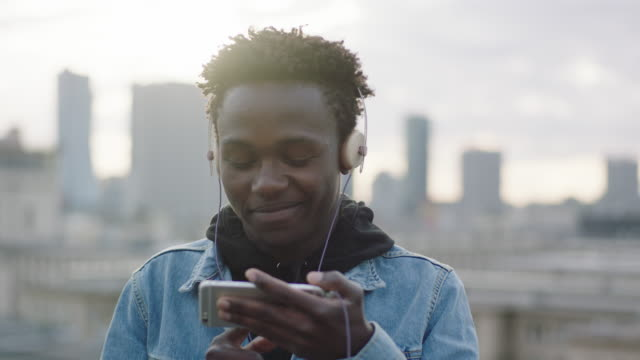 Young man listening music on roof. Changing songs on smartphone video