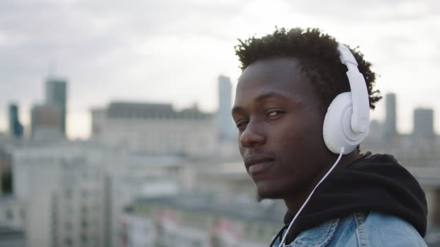 Young man listening music on roof video