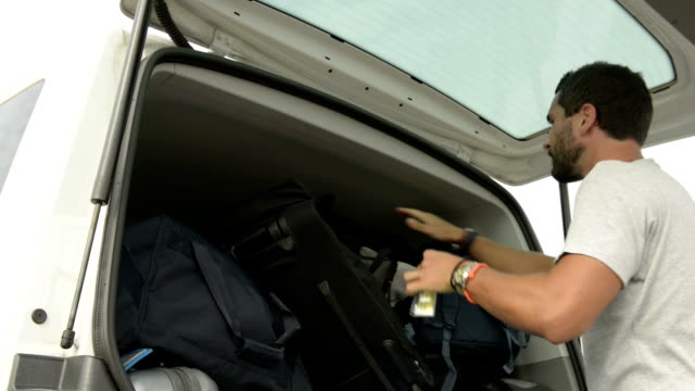 Young man load up the van trunk video HD video