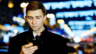 A young man looking at the phone screen, It stands on the background of night city lights video