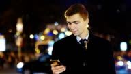 A young man looking at the phone screen, standing on the background of the city at night video