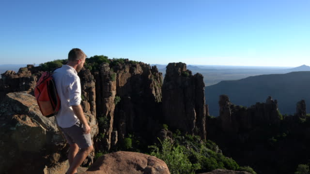 Young man looking at view from mountain top video