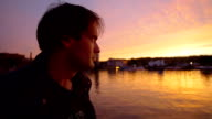 young man looking the sunset in the harbor video