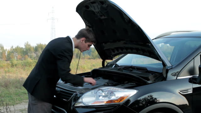 Young man looking under the hood of a car video