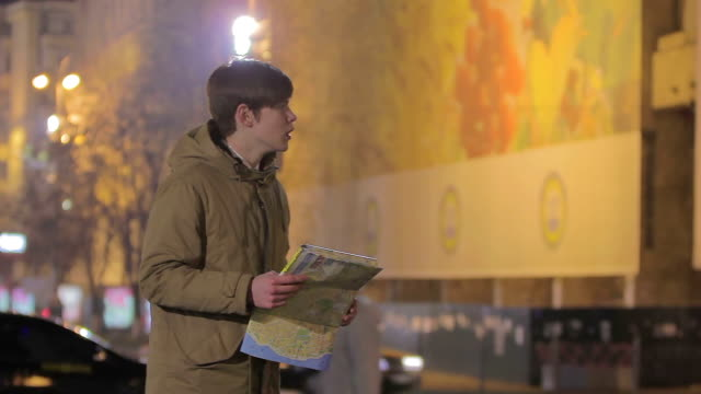Young man lost in big city, looking at map, asking passer-by to show right way video