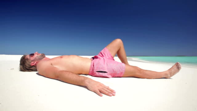 young man lying on a tropical beach video
