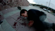 Young man lying on the sidewalk. He's bleeding from the nose video