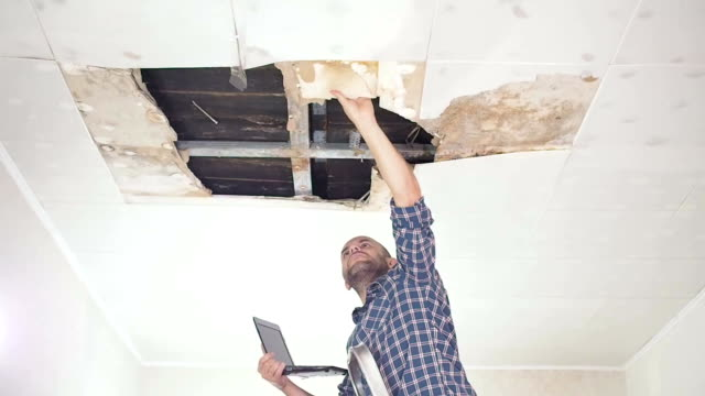 young man makes an emergency inspection of ceiling and use laptop PC. public utilities. Ceiling panels damaged huge hole in roof from rainwater leakage.Water damaged ceiling , Insurance agent. video