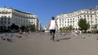 Young Man Making Vault on the Square with Pigeons video