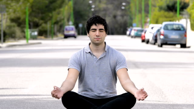young man meditating in the middle of the street, for mindfulness concepts video