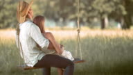 SLO MO Young man on a swing embracing his girlfriend video