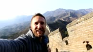 Young man on Great Wall of China taking selfie portrait video
