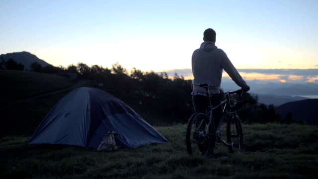 Young man on mountain outdoor look panorama at sunrise sunset with his mountain bike - HD video footage video