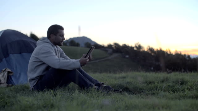 Young man on mountain outdoor seated near his tent use tablet at sunrise sunset - dolly HD video footage video