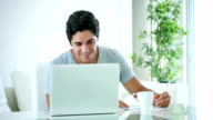 Young man online using a laptop at home video