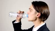 Young man opens a bottle and drink water video